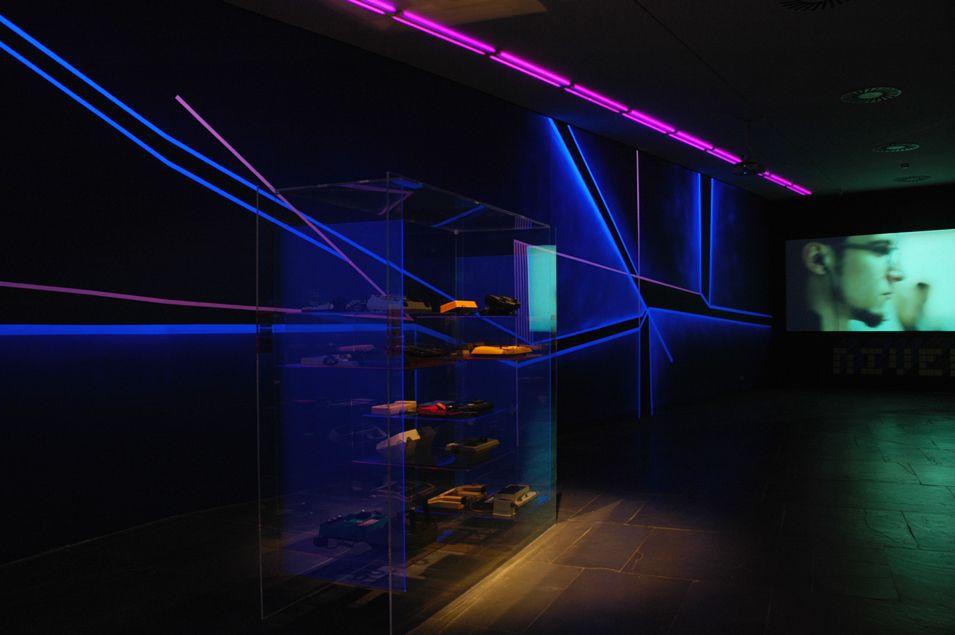 Vitrina de museo con videoconsolas antiguas iluminadas en primer plano y de fondo un muro pintado con pintura flúor y luz negra.